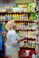 A smiling middle aged woman in a household section of a supermarket