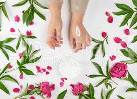 two female hands and a jar with thick cream and burgundy floweri