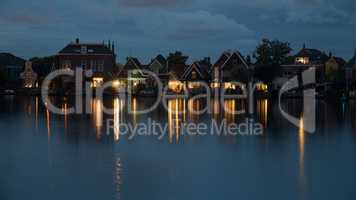 Waterside Dutch village with lights reflection on water at night