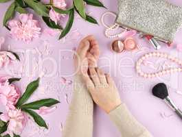 two hands with smooth skin of a young girl and a handbag with co