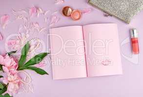 open notebook with blank pink pages, a bouquet of peonies, red l