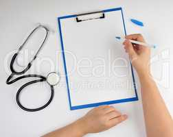 female hand holding a pen for writing a diagnosis or prescriptio