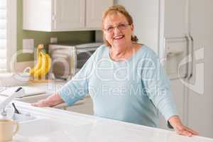 Portrait of A Beautiful Smiling Senior Adult Woman in Kitchen