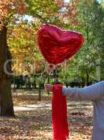 female hand holding a red balloon in the shape of a heart