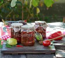 Canned eggplant slices in spicy vegetable sauce in glass jars