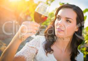 Beautiful Young Adult Woman Inspects Glass of Wine n The Vineyard