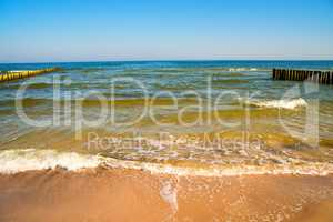 Baltic Sea with groins and surf and blue sky