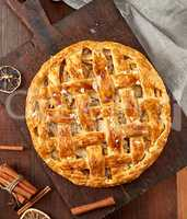 baked whole round apple pie on a brown wooden board