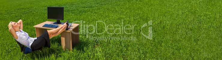 Panorama Businesswoman Relaxing at a Desk In Green Field Banner