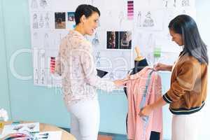 Female fashion designers working together working on garment on dressmaker model