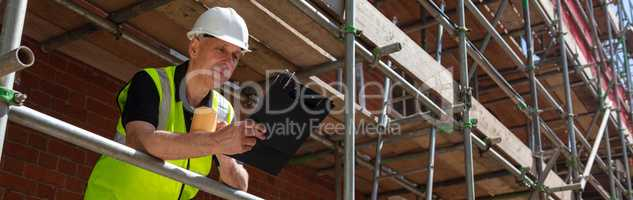 Construction Foreman Builder on Building Site Clipboard and Mug