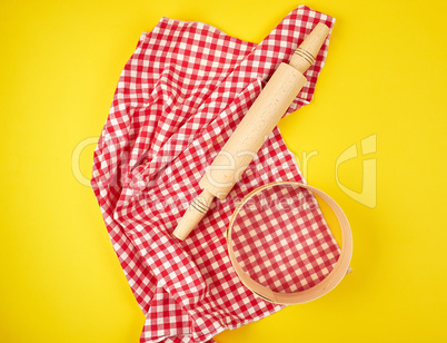 wooden rolling pin on a red textile napkin and a round sieve