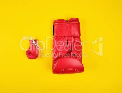 two red boxing gloves on a yellow background