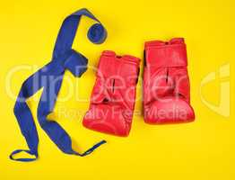 pair of red leather boxing gloves and blue textile bandage