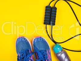 sports expander and water bottle and blue sneakers on a yellow b