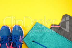 blue women's sneakers and clothes for sports on a yellow  backgr