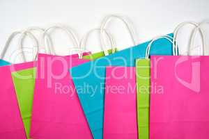 multi-colored paper shopping bags with white handles