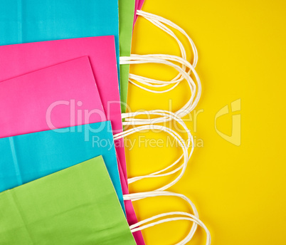 rectangular multi-colored paper shopping bags with white handles