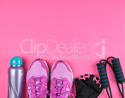 pink women's sneakers, a bottle of water, gloves and a jump rope