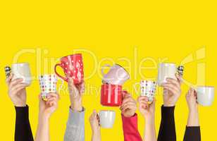 many raised hands up with ceramic cups on a yellow background