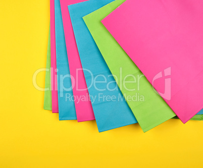 multi-colored paper shopping bags on a yellow background