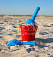 red plastic bucket and blue rake, shovel on the sand
