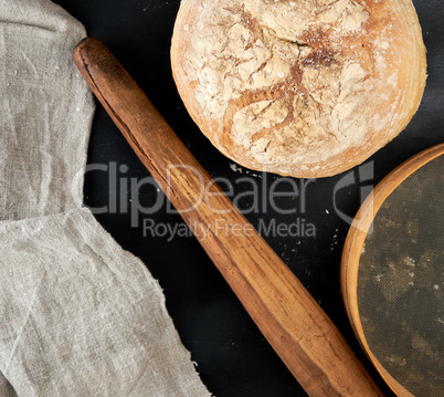 round baked bread and wooden old rolling pin on a black table