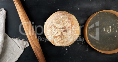 round baked bread and wooden old rolling pin