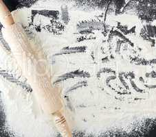 scattered white wheat flour and wooden rolling pin