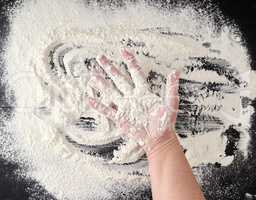 white wheat flour scattered on a black background