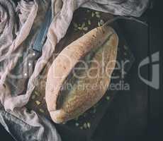 baked crisp oval bread and vintage knife