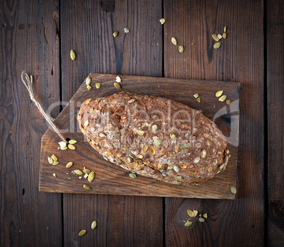 baked oval bread made from rye flour with pumpkin seeds on a woo