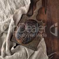 baked rye bread on a gray linen napkin, brown wooden table