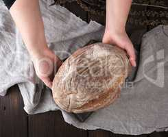 women's hands hold a whole round loaf of rye flour bread
