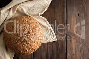 baked round rye bread with sunflower seeds on a beige textile na