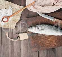 fresh whole sea bass fish and knife on brown cutting board