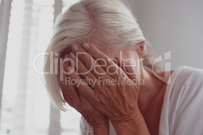 Active senior woman covering face with her hands at home