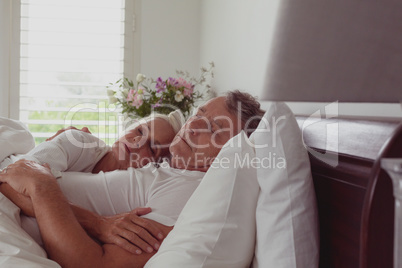 Active senior couple sleeping together in bed in bedroom at comfortable home
