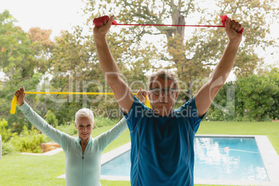 Active senior couple exercising with resistance band in porch at home