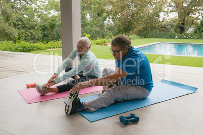Active senior couple doing stretching exercise in the porch at home