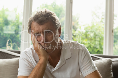 Active senior man with hand on face sitting on sofa in a comfortable home