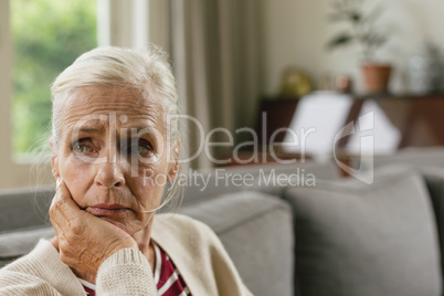 Active senior woman with hand on face sitting on sofa in a comfortable home
