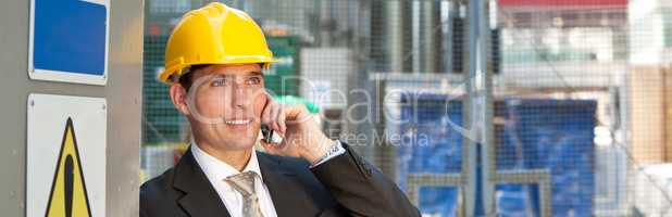 Construction Worker Builder on Building Site Talking on Phone Pa