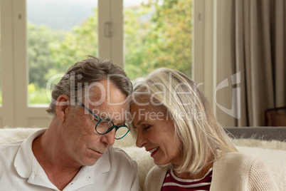 Active senior couple head to head on sofa in a comfortable home