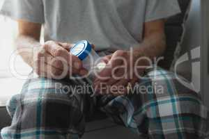 Active senior man taking medicine in bedroom at home