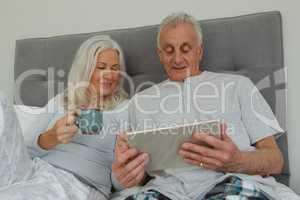 Active senior couple using digital tablet in bedroom