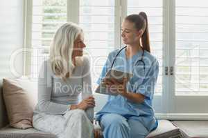 Active senior woman and female doctor using digital tablet on window seat