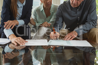 Active senior couple signing an agreement with real estate agent over documents in living room