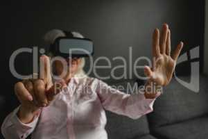 Active senior woman using virtual reality headset in living room