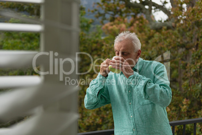 Active senior man drinking coffee on the balcony